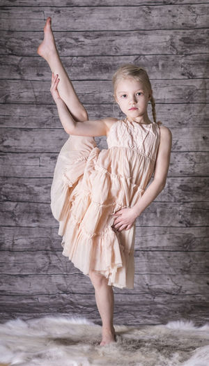 Portrait of cute girl stretching leg against wooden wall