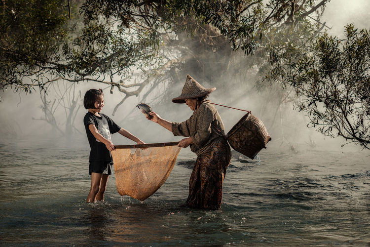 Mother and daughter are fishing at a river in the countryside. Catch Of Fish Day Fisherman Fishing Fishing Industry Full Length Holding Lifestyles Men Nature Nautical Vessel Occupation One Person Outdoors Plant Real People River Standing Three Quarter Length Tree Water Waterfront