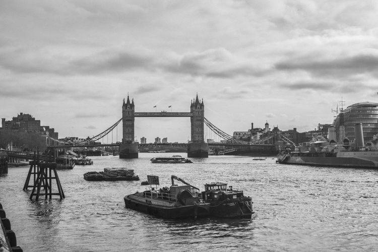 View of tower bridge in the distance looking east up the thames against a moody sky