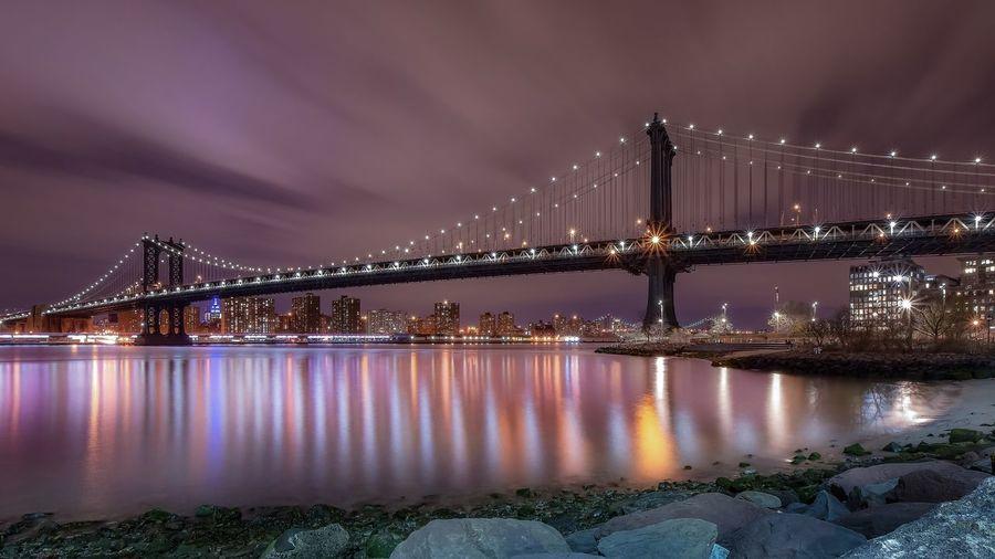 Illuminated manhattan bridge over east river against sky at night