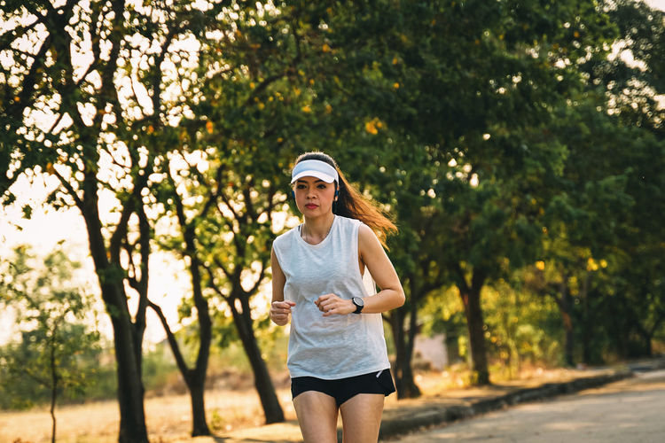 Woman runner does jogging on the city road. Sport and workout. Sport Workout Jogging Running Exercise Plant One Person Tree Three Quarter Length Casual Clothing Young Adult Focus On Foreground Lifestyles Front View Real People Day Leisure Activity Nature Young Women Standing Clothing Sunglasses Outdoors Hairstyle