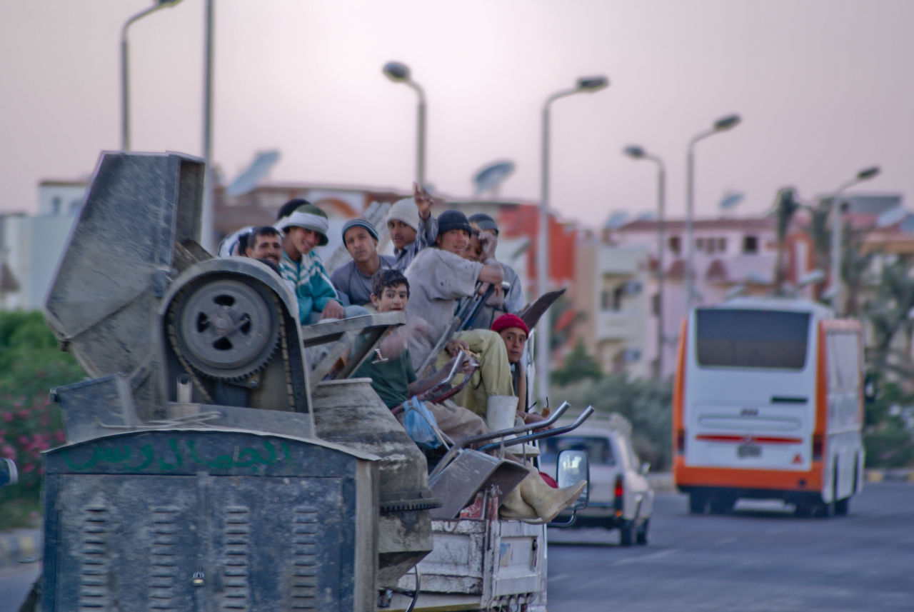 real people, focus on foreground, transportation, sky, outdoors, men, togetherness, day, sitting, architecture, city, people