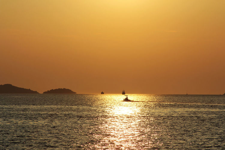 Beauty In Nature Copy Space Horizon Over Water Idyllic Nature Nautical Vessel Orange Color Outdoors Real People Reflection Scenics - Nature Sea Silhouette Sky Sunset Tranquil Scene Tranquility Transportation Water Waterfront My Best Travel Photo