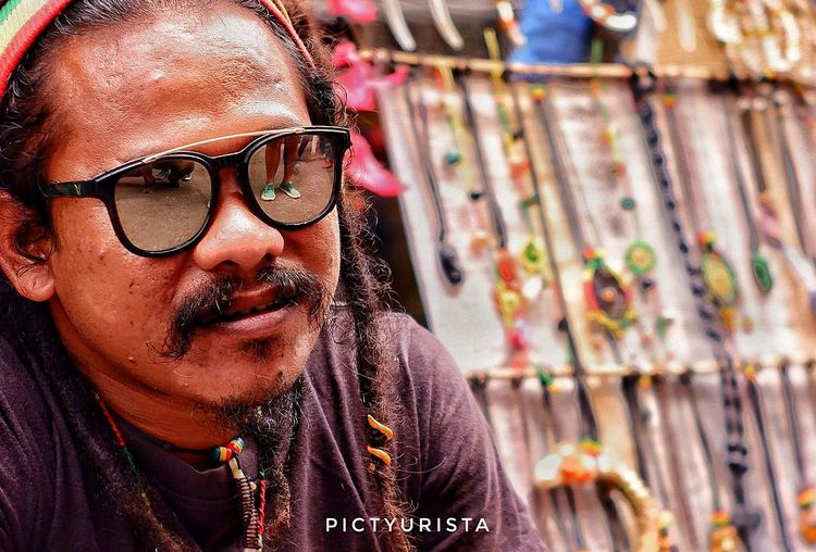 """Rasta forever"" (Cropped) This picture was taken last August 19, 2018 during the celebration of Kadayawan sa Davao 2018. He's a vendor of colorful accessories, with amazing dreadlock hair. Good thing is, he allowed us to take some snaps. Dreadlocks Reggae RASTA Fujifilm XT100 7artisans Randomphotos Composition Hobbyistphotographer Ndfiltered Philippines Landscapephotography Photographer Fuji Newbie Lensculture Streetphotographyworldwide Street_focus_on Streetphotography Streets_storytelling Streetsleaks Streetclassics Streetphotographycommunit DavaoCity Kadayawan2018 Women Human Face Sunglasses Close-up Glasses"