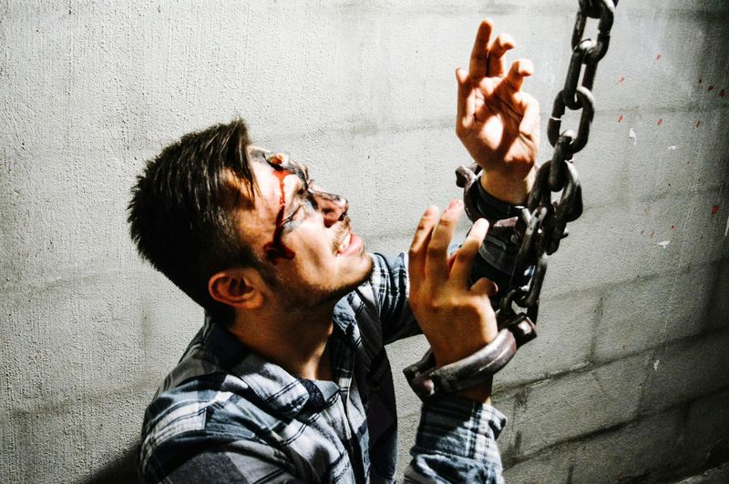 Injured man with hand cuffed by wall