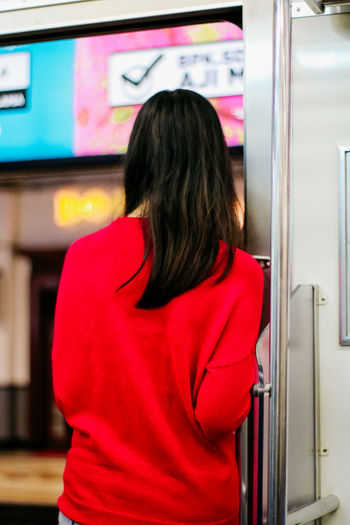 Standing One Person Women Rear View Adult Real People Leisure Activity Lifestyles Indoors  Long Hair Casual Clothing Red Hairstyle Waist Up Hair Retail  Shopping Focus On Foreground Store Vending Machine