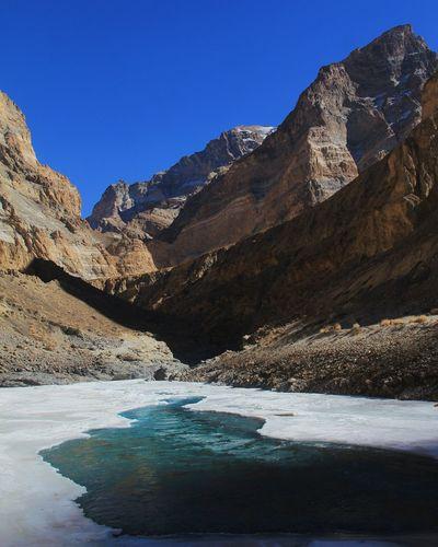 Frozen lake against mountains
