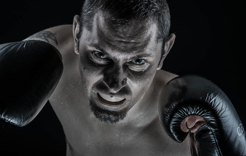 Portrait of boxer against black background
