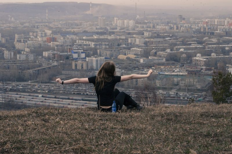 Rear view of woman with arms outstretched relaxing on grassy hill