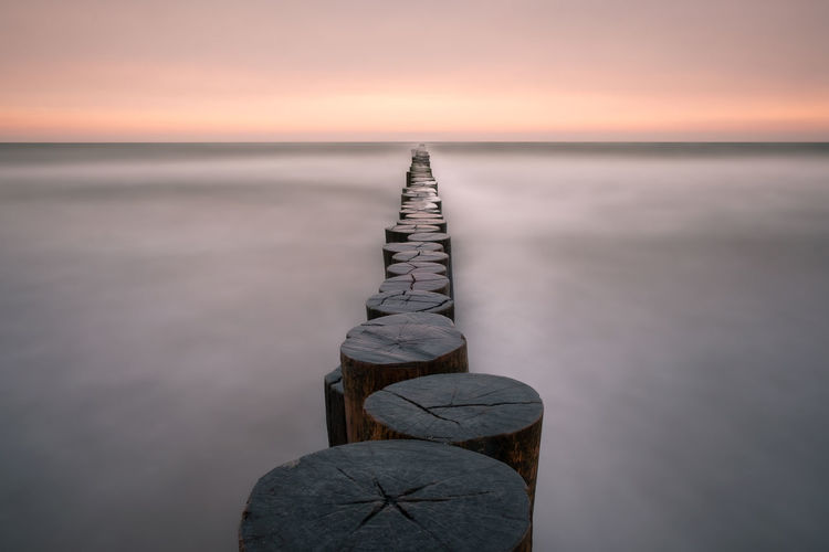 Groynes At Beach In Silent Sea During Sunset