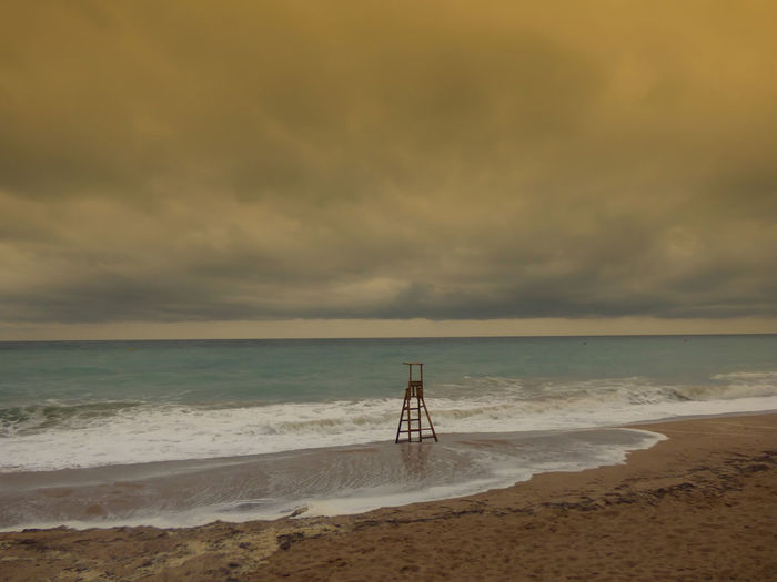 Lifeguard chair on shore at beach against cloudy sky during sunset