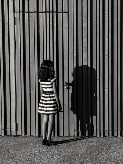 Rear View Of Girl Standing By Corrugated Door