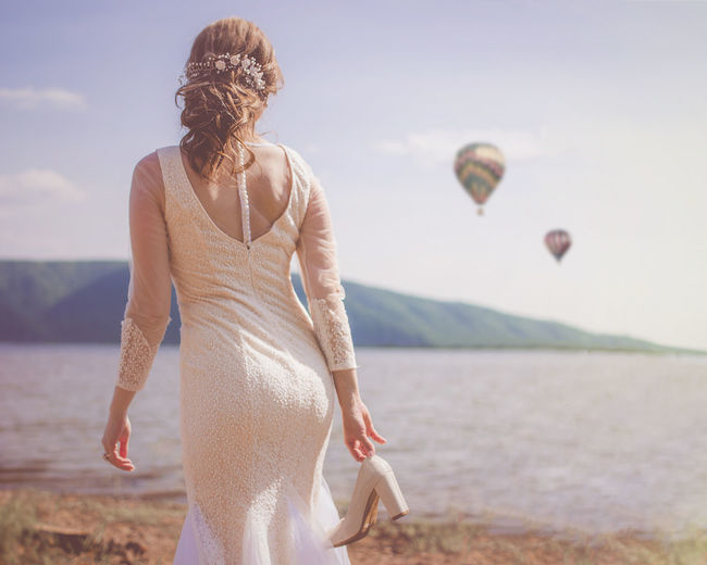 Rear view of bride standing against air balloons