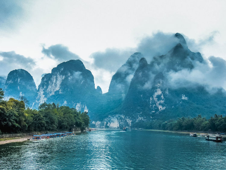 Beautiful Li River landscape in the mist Background Beauty In Nature Beauty In Nature Blue Sky Boat Countryside Day Fog Guilin Hills Karst Mountain Landscape Li River Lijiang Mist Natural Heritage Nature Nature Photography Outdoors Painting River Scenery Transportation Travel Destinations Water