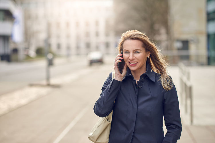 Woman Talking On Phone On Street In City