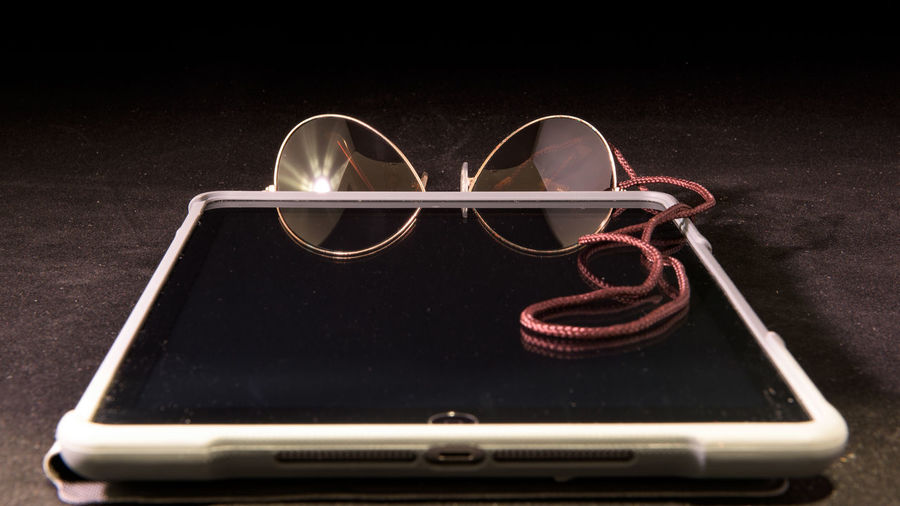 Close-Up Of Digital Tablet With Sunglasses On Table