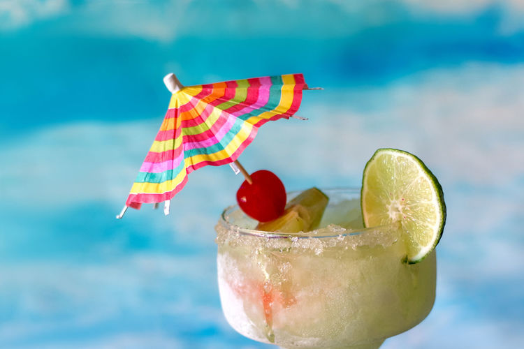 frozen margarita drinks with lime and cherry garnish and a colorful drink umbrella Frozen Margarita Adult Drinks Alcholic Beverage Alcohol Cherry Garnish Citrus Fruit Close-up Cocktail Cold Drink Drink Drink Umbrella Drinking Glass Food Food And Drink Freshness Fruit Fruit Garnish Glass Lime Refreshment SLICE Slushy Ice Summer Summer Beach Drinks Summertime Drinks