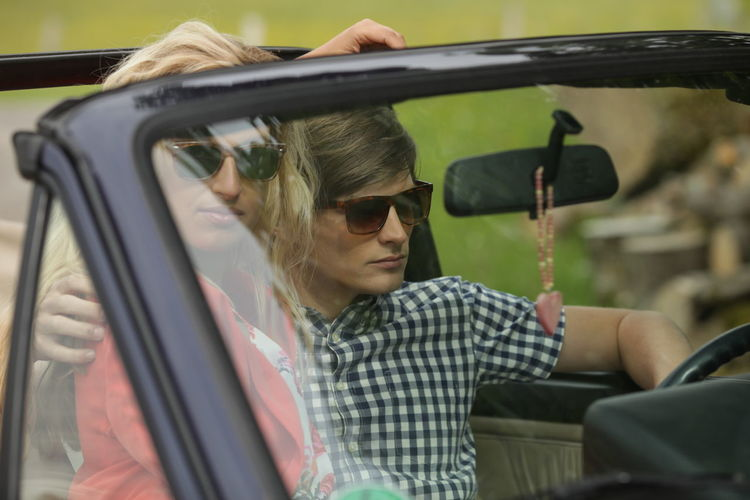 Young Couple Traveling In Car
