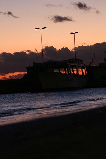 Silhouette boats on sea against sky during sunset