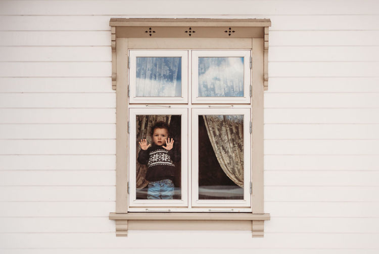 Portrait of girl standing against window of building
