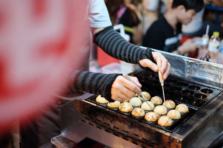 Cropped Image Of Person Cooking Takoyaki At Food Market