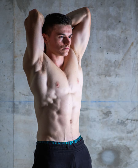 Young muscular man standing against wall