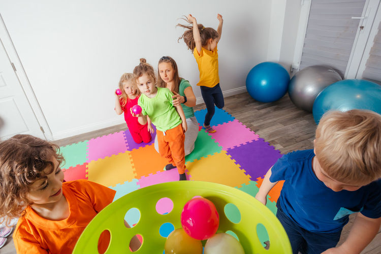 Rear view of people playing with multi colored balloons