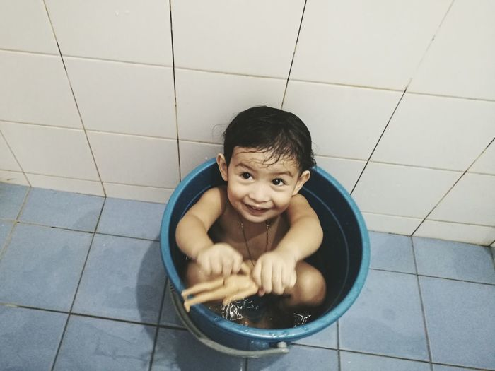 High angle view of naked smiling girl sitting in bucket