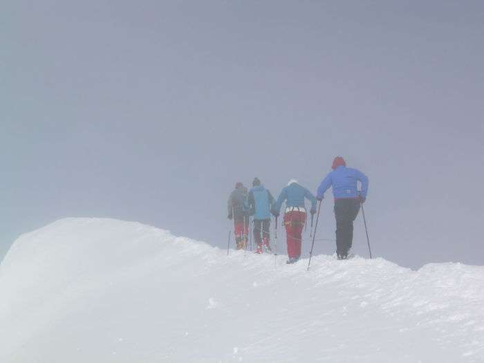 Rear view of friends walking on snowcapped mountain during winter