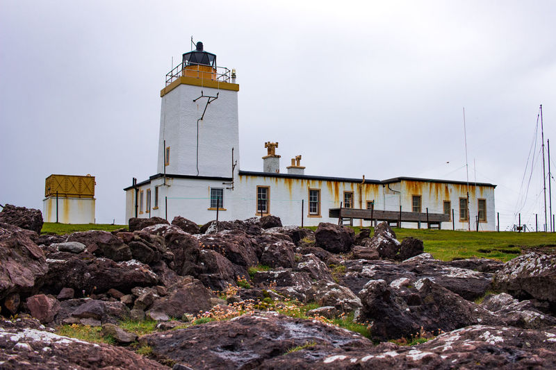 Lighthouse amidst rocks and buildings against sky