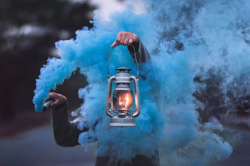 Person Holding Illuminated Lantern Amidst Blue Smoke