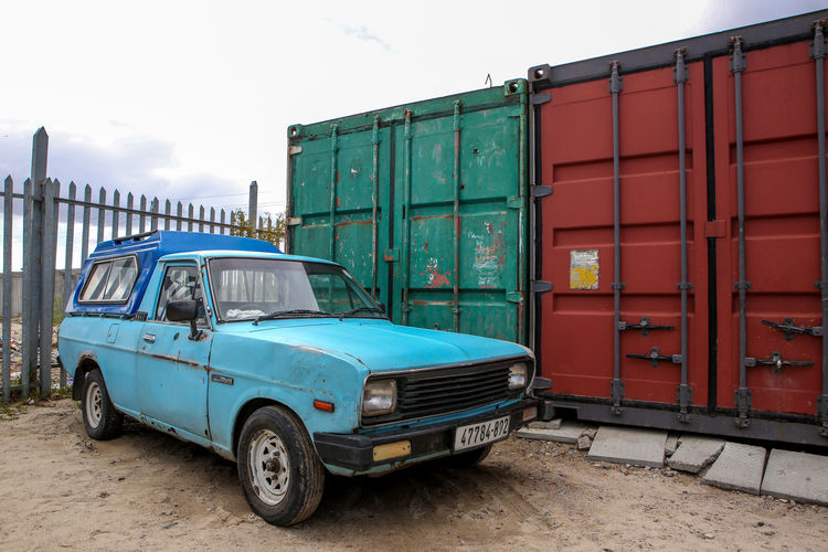 Car stansing in front of some overseas containers Blikkiesdorp Car Containers Day Land Vehicle Mode Of Transport No People Outdoors Rusty Sky Stationary Township Transportation