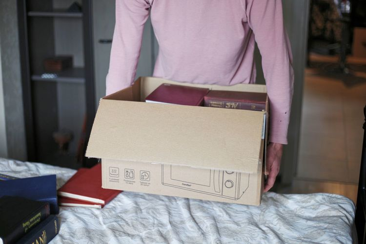 Midsection of man holding book at home