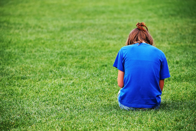 Rear view of woman sitting on grassy field