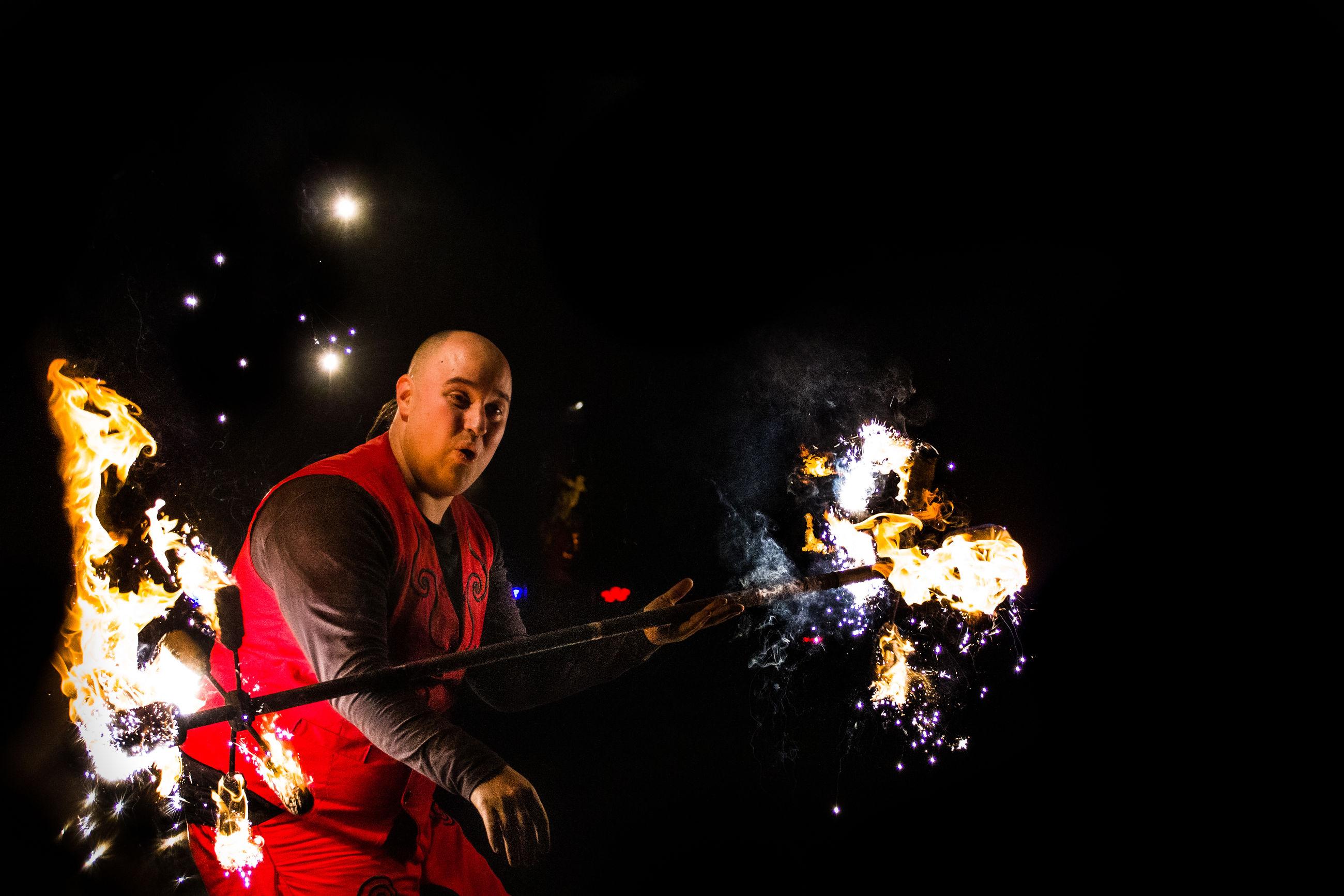 LOW ANGLE VIEW OF MAN HOLDING ILLUMINATED BONFIRE