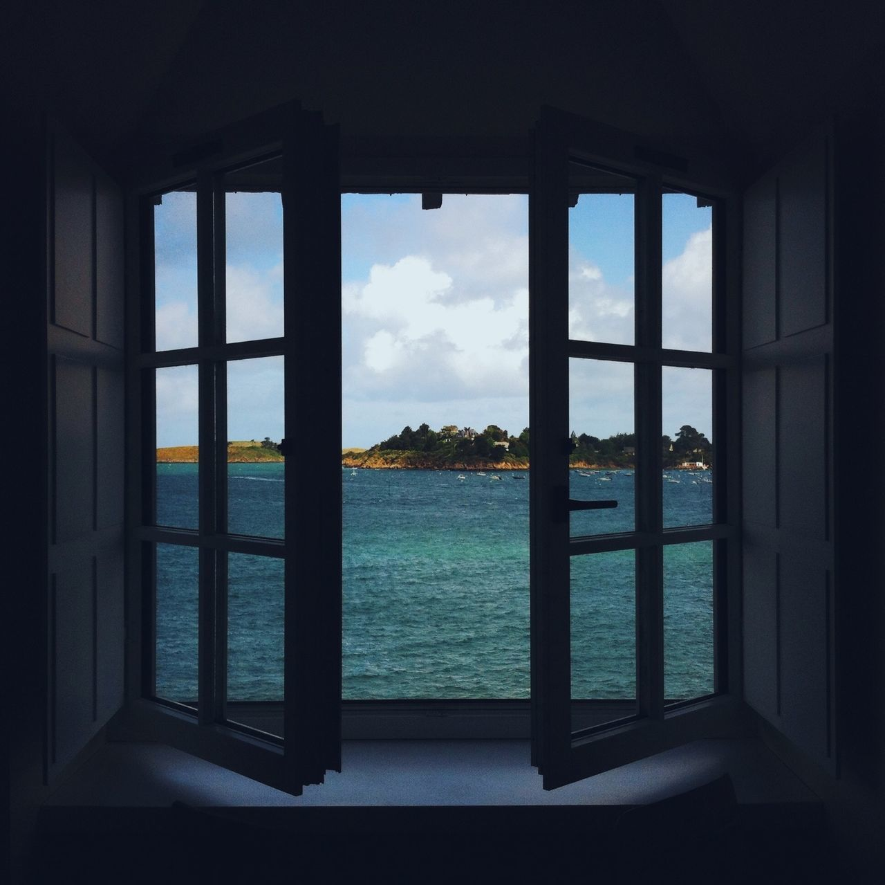 Window overlooking sea against clouds