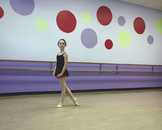 Full Length Of Girl Practicing Ballet At Studio