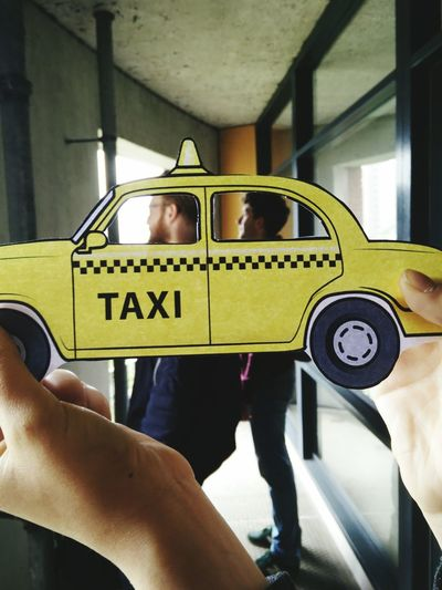 Cropped hand of man holding yellow taxi paper art against friends