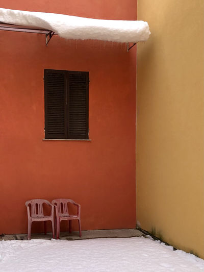 Empty chairs and tables against orange wall of building