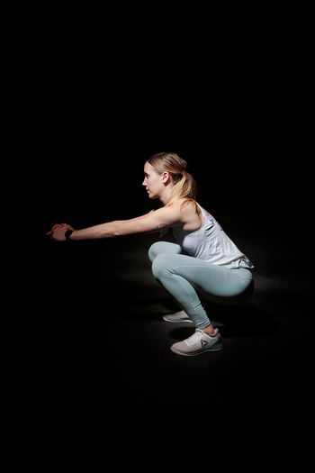 Young woman doing gym excercise against black background Adult Sport Activity Athletic Attractive Beautiful Body Exercise Female Fit Fitness Girl Gym Health Healthy Lifestyle Muscle One person Pilates Pose Slim Sportswear Studio Training Weight Wellness Woman Workout Young