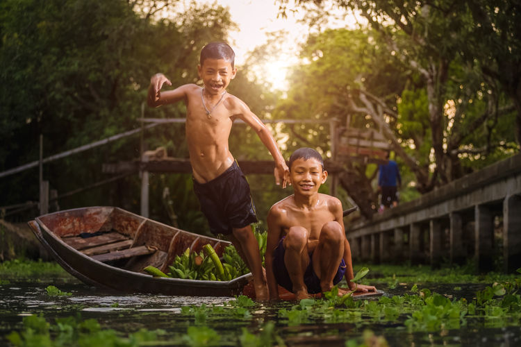 Portrait of happy shirtless boy with brother jumping in river