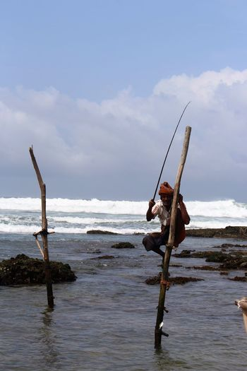 Stilt fisherman caught a fish Sri Lanka Sea Water Sky Men Real People Horizon Over Water One Person Full Length Outdoors Nature Day Scenics
