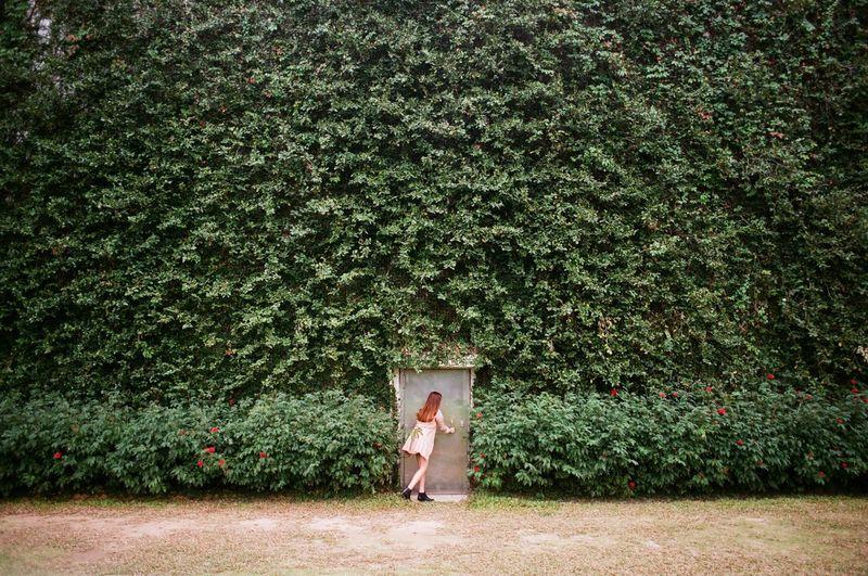 Woman Entering Door In Greenery