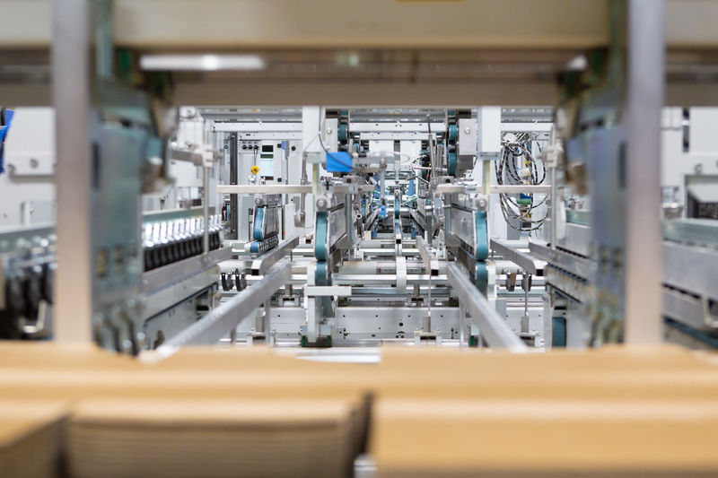 Printing and cutting packaging industry machine Industry Factory Equipment Technology Manufacturing Equipment Machinery Business Selective Focus No People Manufacturing In A Row Food And Drink Industry Production Line Efficiency Focus On Background Order Food And Drink Conveyor Belt Silver Colored Distillation Printing Cutting Board Industry Measuring Measurement Occupation Horizontal Packaging Industry Cardboard Warehouse