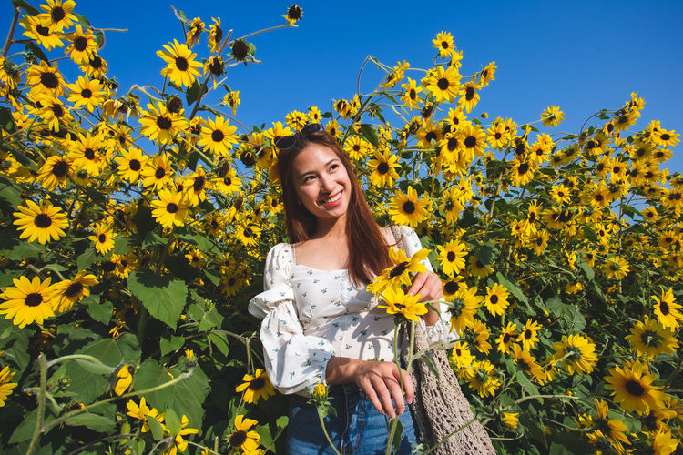 Portrait of smiling young woman against yellow flowering plants