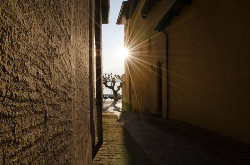 Narrow Street with Sunbeam Sunlight Sunny Wall Architecture Building Building Exterior Built Structure City Day Diminishing Perspective Direction Lens Flare Narrow No People Outdoors Sky Street Sun Sunbeam Sunlight The Way Forward Walkway Wall - Building Feature