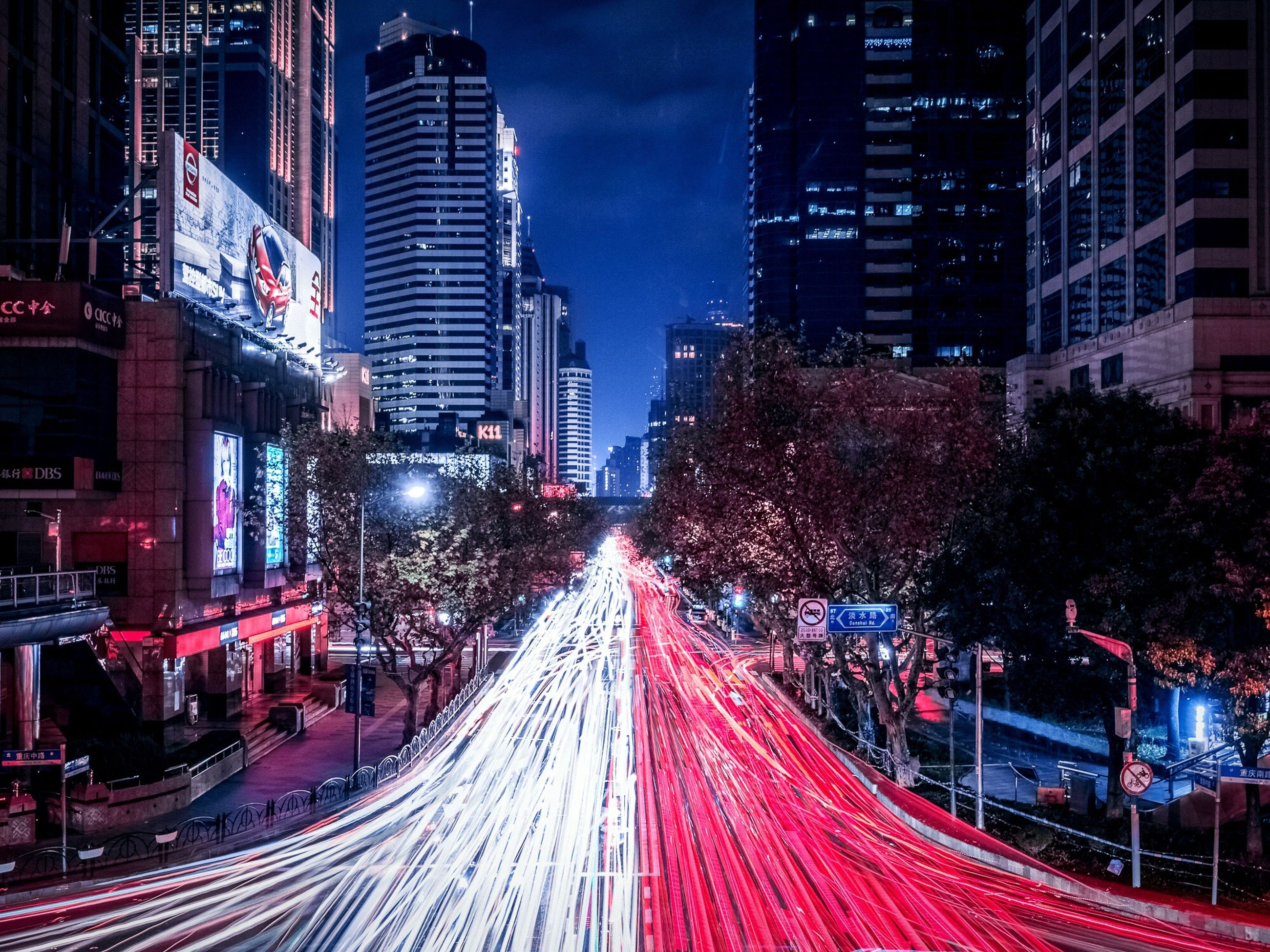 city, illuminated, building exterior, transportation, architecture, night, built structure, long exposure, the way forward, light trail, road, city life, street, high angle view, city street, motion, speed, diminishing perspective, traffic, vanishing point