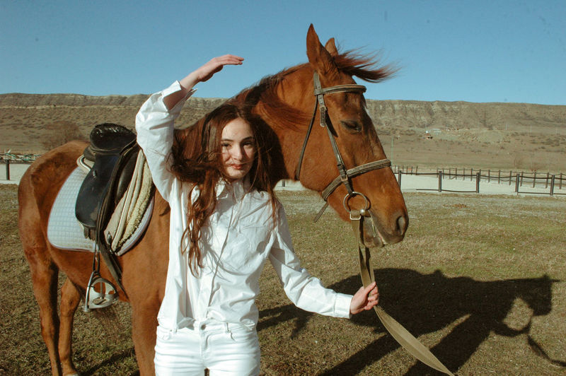 Portrait of young woman with horse standing on land against clear sky