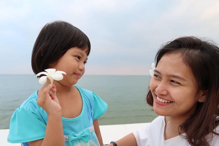 Portrait of smiling woman against sea against sky