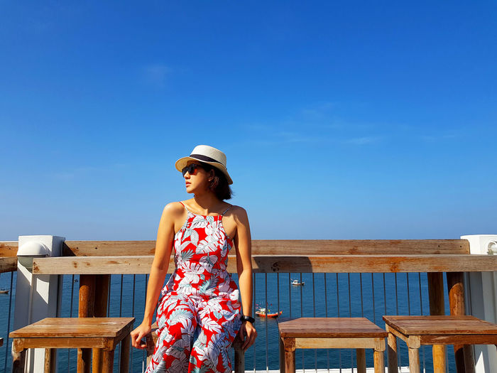 Woman standing by railing against blue sky